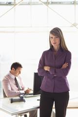Geschäftsfrau, die Arme verschränkt, männlicher Kollege im Hintergrund arbeiten