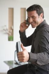 Geschäftsmann mit Handy, Daumen nach oben