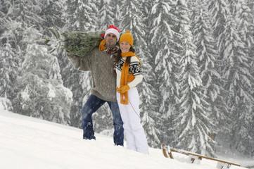 Paar im Schnee, Mann mit Weihnachtsbaum, Frau zieht Schlitten