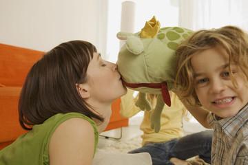 Mutter spielt mit Kindern, sie küssen ein Spielzeug Frosch