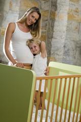 Schwangere Mutter und Tochter (3-4), lächelnd