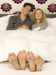 Junges Paare liegt im Bett, Nahaufnahme von Füßen