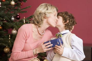 Kleiner Junge mit Weihnachtsgeschenk für Großmutter