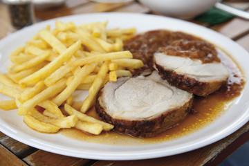 Gebratenes Schweinefleisch mit Pommes frites und Zwiebelsauce