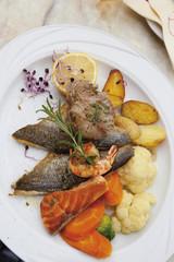 Fisch auf Teller mit Gemüse und Zitrone garniert
