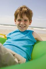 Deutschland, Ostsee, Junge (8-9) sitzt auf Schwimmreifen am Strand