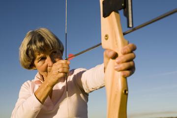 Ältere Frau mit Pfeil und Bogen
