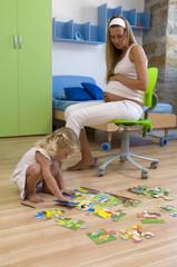 Schwangere Mutter und Tochter (3-4) mit einem Puzzle auf dem Boden