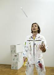 Mann jongliert mit Pinsel und Zollstock