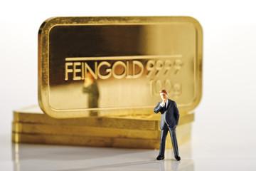 Geschäftsmannfigürchen, im Hintergrund Goldbarren