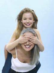 Mädchen sitzt auf Rücken einer Frau und hält ihr die Augen zu