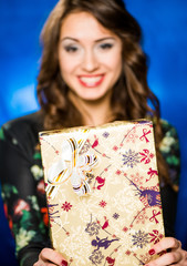 smiling brunet with gift on a blue