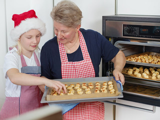 Grandmother and child baking biscuits for christmas