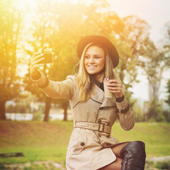 Gorgeous stylish young woman taking a selfie outdoors in autumn