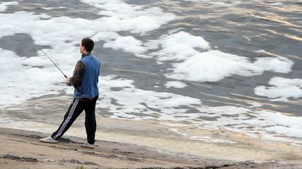 Young man fishing on a lake