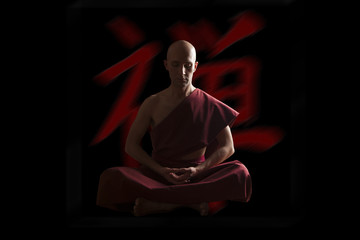buddhist monk in meditation pose  with zen symbol on the backgro