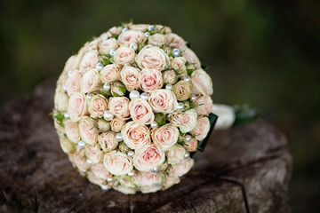 Pastel wedding bouquet with roses on wood