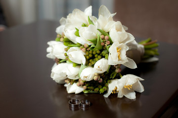 Tulip wedding bouquet with rings on table