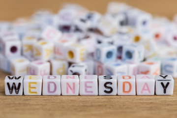 Wednesday written in letter beads on wood background