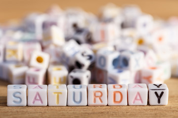 Saturday written in letter beads on wood background