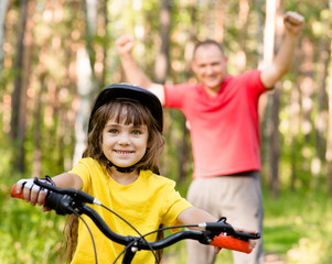 happy father rejoices that her daughter learned to ride a bike