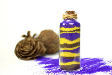 Purple and yellow sand in bottle
