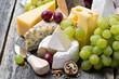 Leinwandbild Motiv assortment of fresh cheeses and grapes on a wooden background