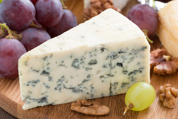 blue cheese on a wooden board and fresh grapes