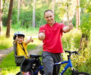 happy father and his cute daughter outdoors in forest on a bike