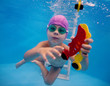 little boy trains in the pool to catch the toy under water