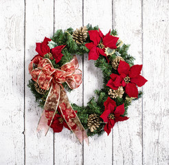 Christmas wreath against white wooden background