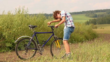 Young man with bicycle in a wheat field