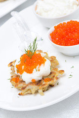 potato pancakes with red caviar and sour cream on the plate