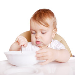 Baby eating by himself in high chair.