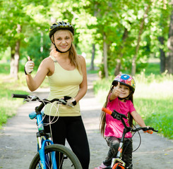 happy mother and daughter having fun, riding a bicycle and showi
