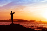 Fototapety man taking photos of sunset with mobile phone