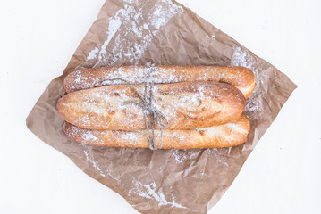 Freshly backed baguettes on a brown paper