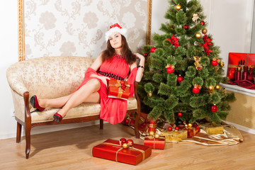 smiling lass wearing red dress and Christmas hat sits oa sofa