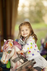 Happy Little Girl Riding On a Horse In Amusement Park Outdoor