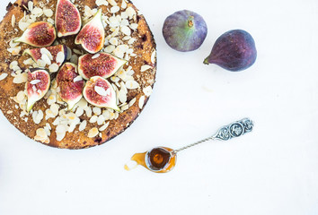 Fig cake with fresh figs, honey and almond flakes on white