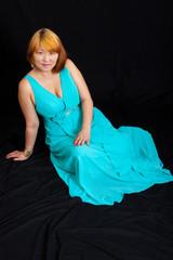 blonde girl wearing a long blue dress sitting