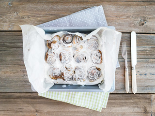 Cinnamon buns with cream-cheese icing in a baking dish over a ru