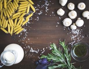 Mushroom pasta ingredients: penne, mushrooms, a jug of cream, pe