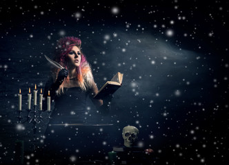 Beautiful witch making witchcraft over the smoky background