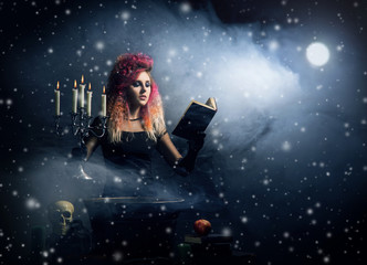Beautiful witch making witchcraft on a snowy background