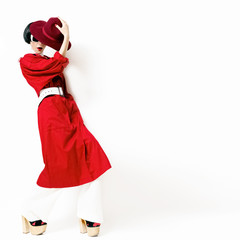 glamorous lady in trendy vintage red raincoat and hat on a white