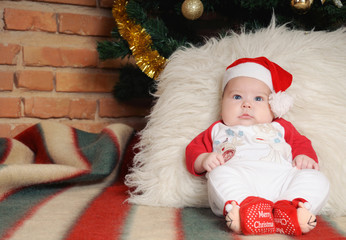 cute newborn baby in Santa hat sitting near Christmas tree