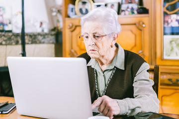 Senior woman with laptop at home
