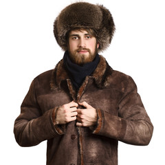 Fashion portrait of young handsome bearded man in the coat