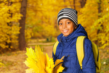 Portrait of cute African boy with leaves bunch